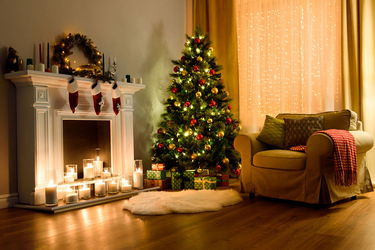 Christmas tree next to a fireplace with lit candles