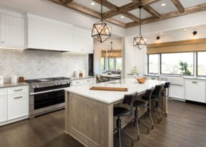 Kitchen interior with island, sink, cabinets, and hardwood floors in new luxury home. Includes elegant pendant light fixtures, under-cabinet lighting, and recessed lighting in wood beam ceiling
