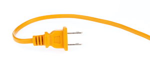 Unplugged orange electric cord. Reduce phantom energy by unplugging unused devices and appliances.